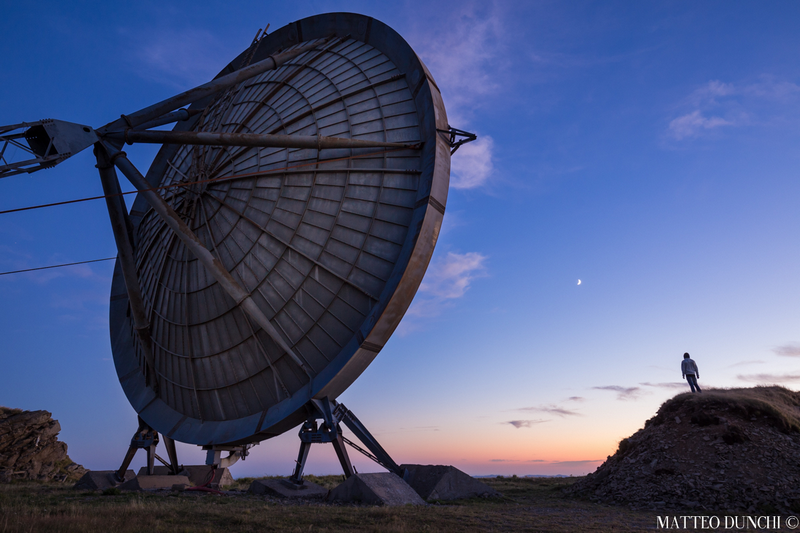 """""""Aiming at the Moon"""" - Self portrait in an abandoned ex-NATO base in Northern Tuscany with 20m radio dishes. Photo by Matteo Dunchi."""