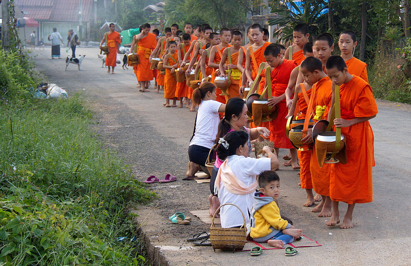 People offering food to Buddhist monks.