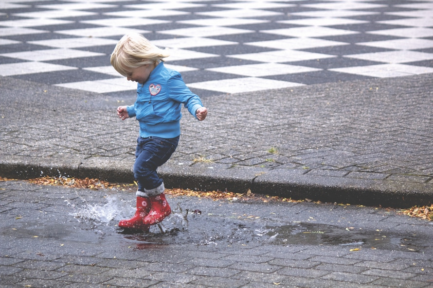 Child playing in a puddle.